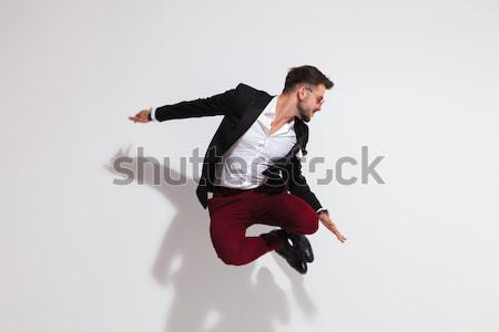 smart casual man jumping and looking down to side Stock photo © feedough