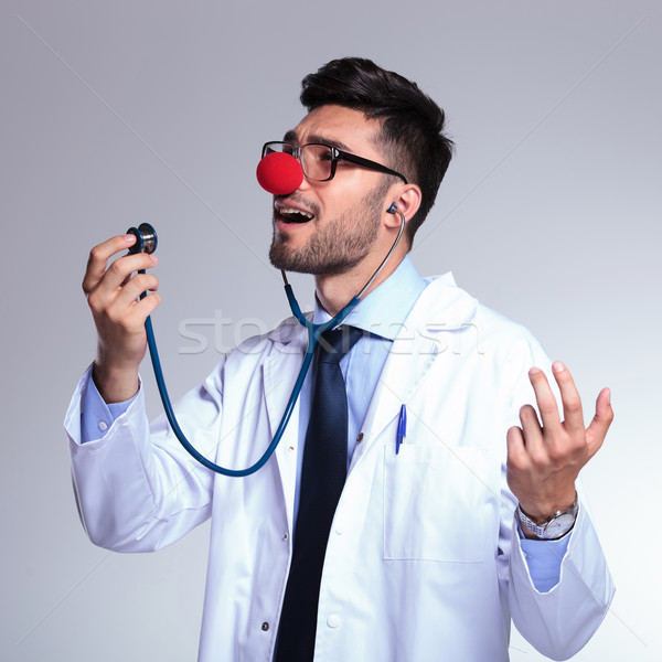 young doctor with red nose singing in the stethoscope Stock photo © feedough