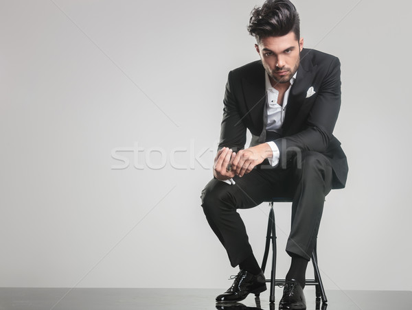 Elegant young man in tuxedo sitting on a stool  Stock photo © feedough