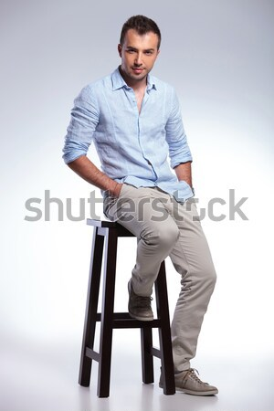man closing his jacket while sitting on a chiar. Stock photo © feedough