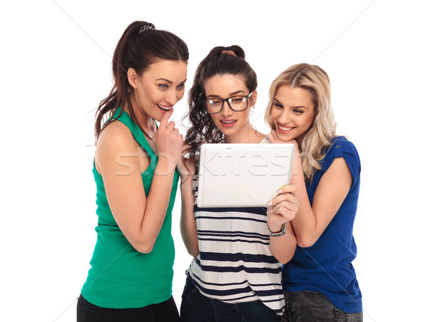 three amazed  women looking at the screen of a tablet  Stock photo © feedough
