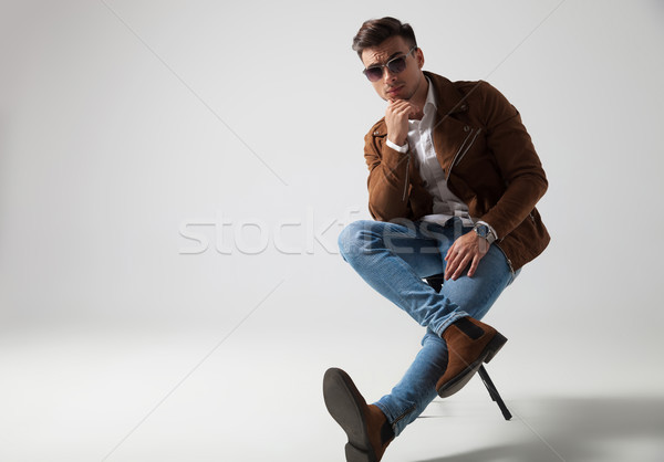 relaxed casual man sitting with legs crossed and thinks , Stock photo © feedough