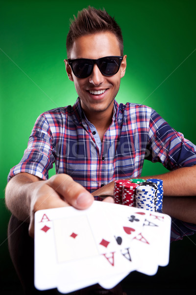 Young casual man showing his poker hand Stock photo © feedough