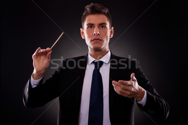 Young businessman directing with a conductor's stick Stock photo © feedough