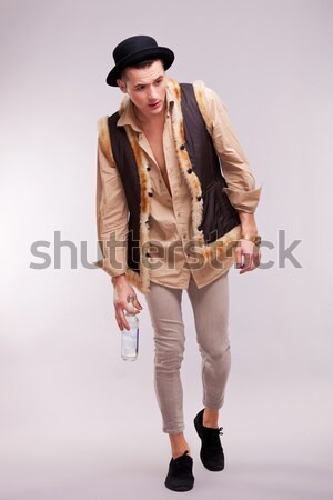 Stock photo: casual man looks away with straw in mouth and hand on hat