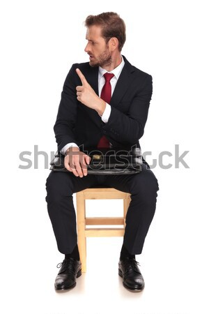 man in tuxedo looking down while sitting on a stool, Stock photo © feedough