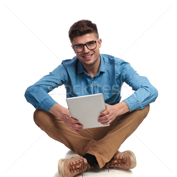 seated young casual man holding tablet  Stock photo © feedough