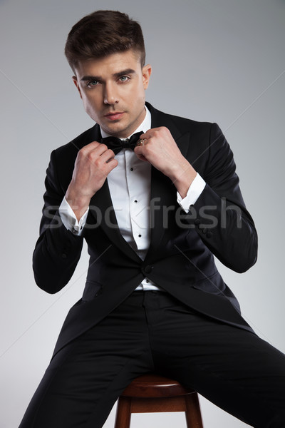 seated handsome man in black tuxedo fixing his bowtie Stock photo © feedough