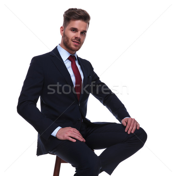 attractive businessman in navy suit resting on wooden chair Stock photo © feedough