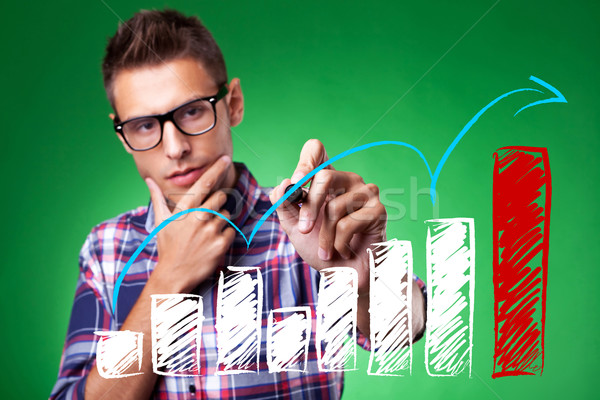 casual man with glasses drawing a rising arrow Stock photo © feedough