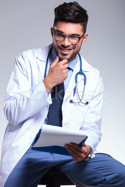 seated young doctor with hand at chin Stock photo © feedough