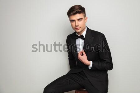 elegant man holding tuxedo's collar and looks to side Stock photo © feedough