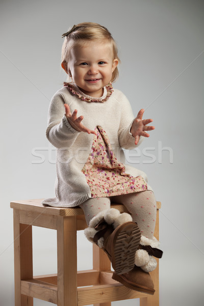 eager little girl is sitting on a chair  Stock photo © feedough