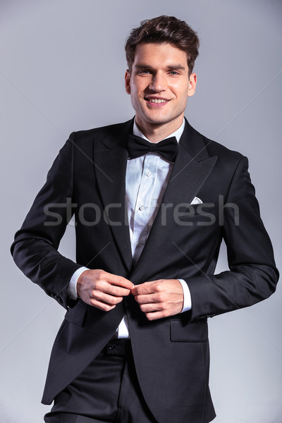 Smiling young business man unbuttoning his tuxedo Stock photo © feedough