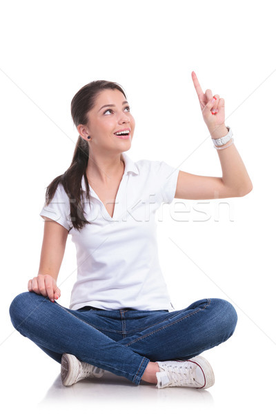 casual woman sits & points up Stock photo © feedough