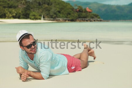man sits on the beach and holds his hat Stock photo © feedough