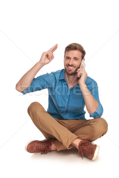 happy seated man talks on the phone and greets everyone  Stock photo © feedough
