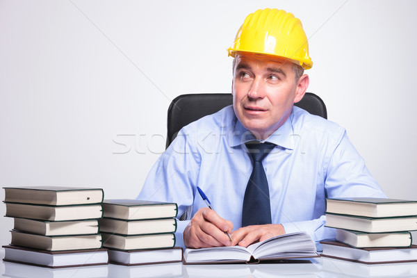 old engineer writes at desk while pondering Stock photo © feedough