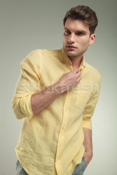 Attractive young business man closing his yellow shirt. Stock photo © feedough