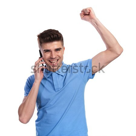 ecstatic young man screaming of joy while talking on phone Stock photo © feedough