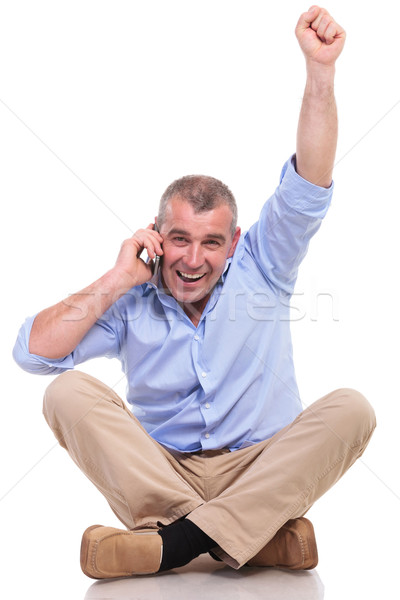casual old man sits and cheers while on phone Stock photo © feedough