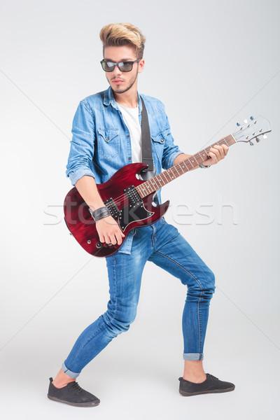 artist playing guitar in studio while posing looking away Stock photo © feedough