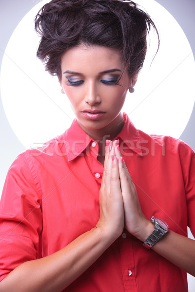 young woman looks down while praying Stock photo © feedough