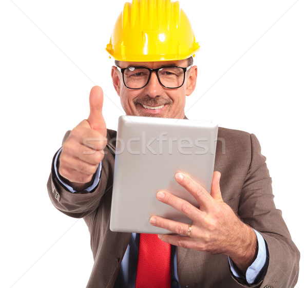 old construction engineer reading good news on his tablet pad Stock photo © feedough
