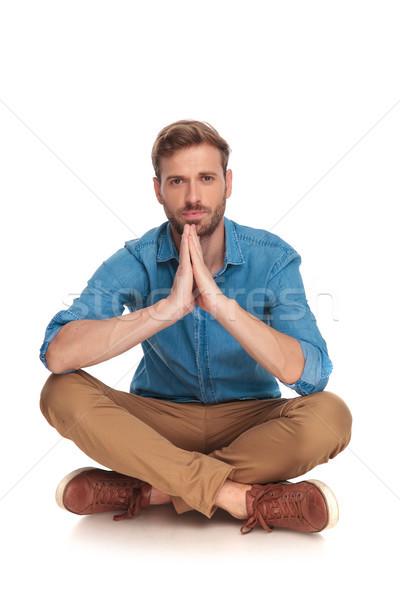 Jóvenes casual hombre sesión rezando blanco Foto stock © feedough