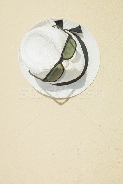 hat with black strap and sunglasses on the beach Stock photo © feedough