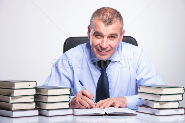 old business man writes at desk full of books Stock photo © feedough