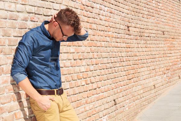 Casual homem em pé chateado parede de tijolos moço Foto stock © feedough