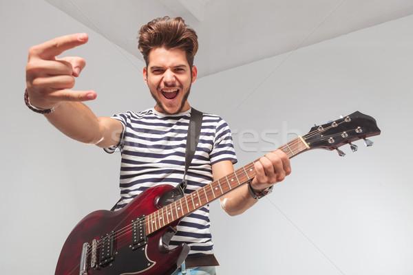 Uomo urlando giocare chitarra guardando verso il basso giovane Foto d'archivio © feedough