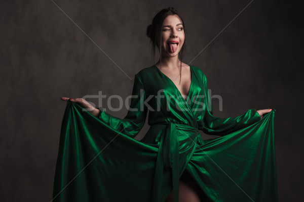 joyful woman holding her green gown makes a crazy face Stock photo © feedough