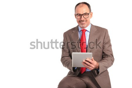mature man in suit thinking and using his tablet Stock photo © feedough