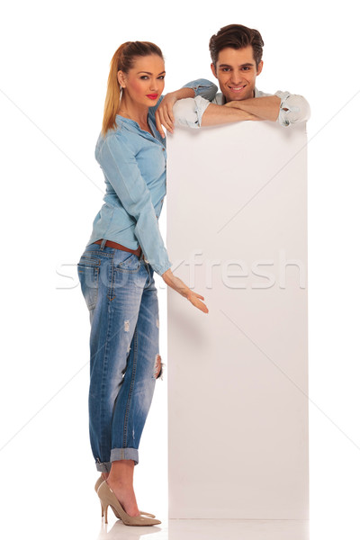 man stands behind white sign while woman is presenting Stock photo © feedough