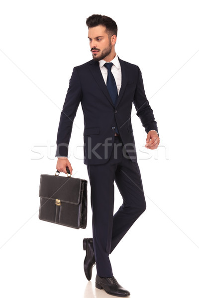 young business man carrying briefcase is walking and looks back  Stock photo © feedough