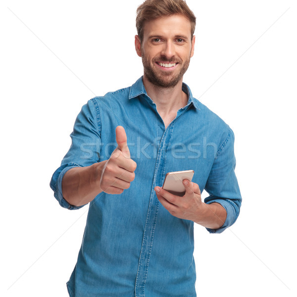 man reading good news on his phone and makes ok Stock photo © feedough