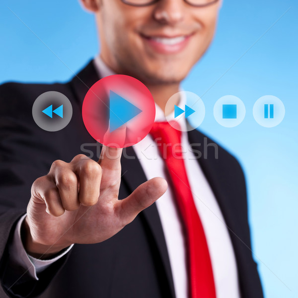 Stock photo: business man pushing a play button