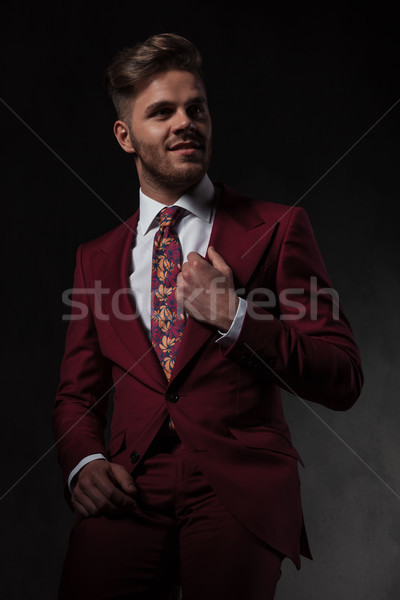 smiling man arranging his red suit collar looks to side Stock photo © feedough