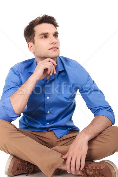 Pensive jeune homme séance jambes croisées caméra Photo stock © feedough