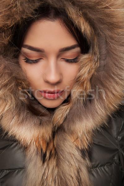 beautiful woman wearing fur hood looks down Stock photo © feedough