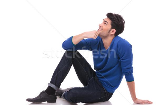 ülő fiatalember farmernadrág póló felfelé néz oldalnézet Stock fotó © feedough