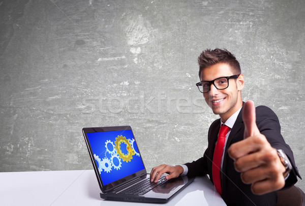 satisfied business man working on laptop and making ok sign Stock photo © feedough