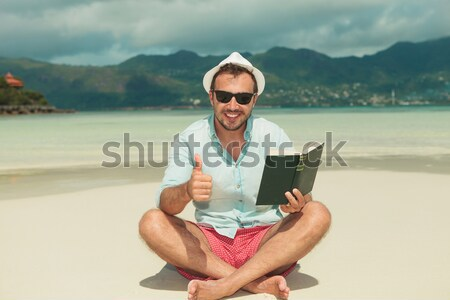 smiling man reading on  tablet  while sitting down the beach Stock photo © feedough