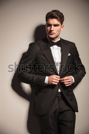 Young elegant business man arranging his tuxedo. Stock photo © feedough
