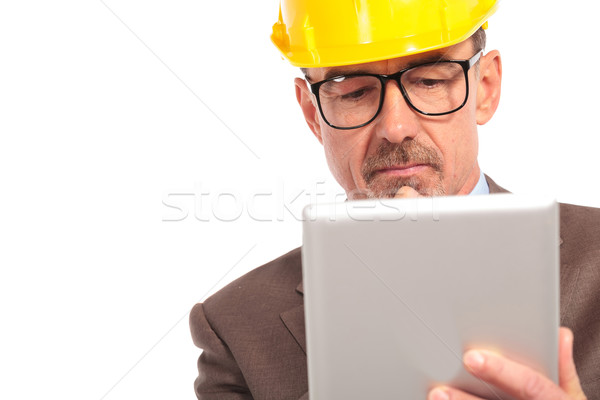 concerned senior construction engineer reading on his tablet  Stock photo © feedough