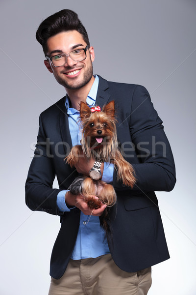 casual young man holds puppy in both hands Stock photo © feedough