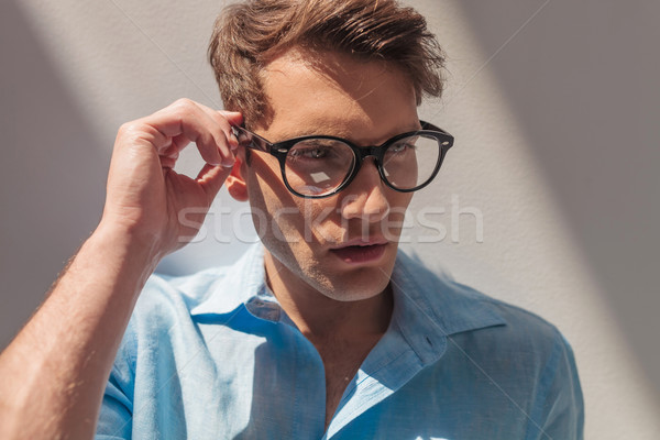 casual man looking away while fixing his glasses. Stock photo © feedough