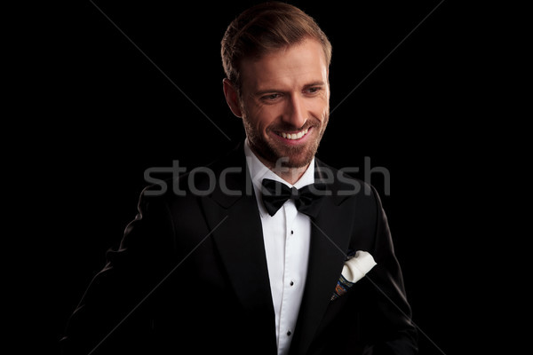 laughing young man in tuxedo and bowtie looks down Stock photo © feedough